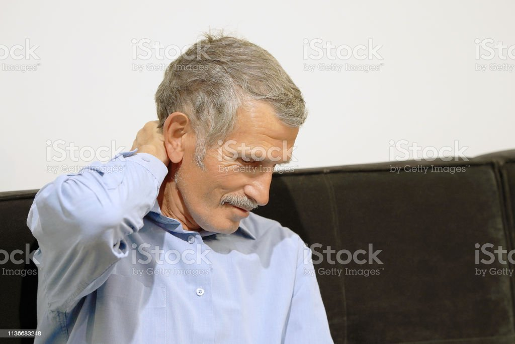 Elderly Man suffering from neck pain at home on couch. Males sense of...