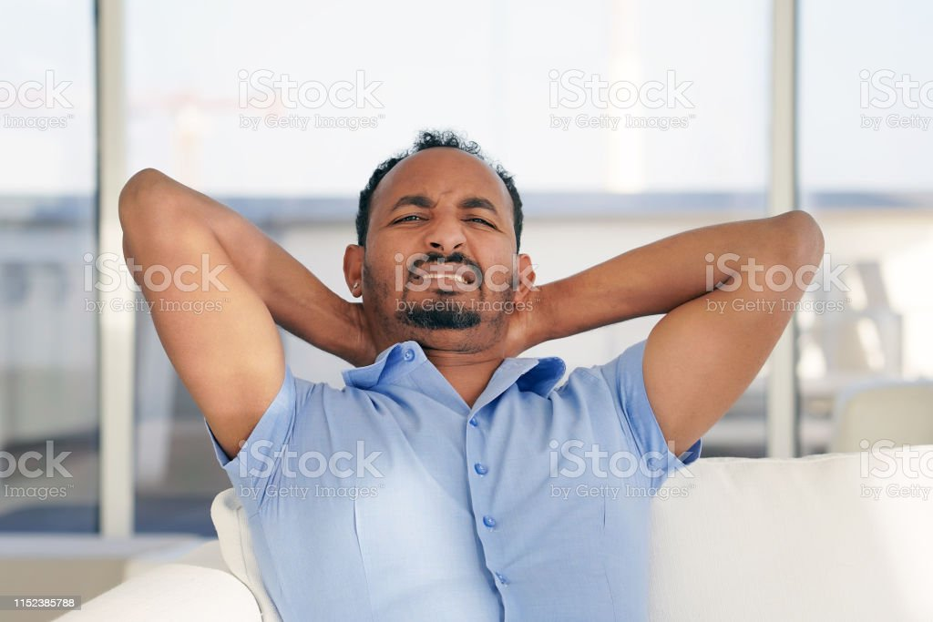 Man suffering from neck pain at home on couch. Males sense of...