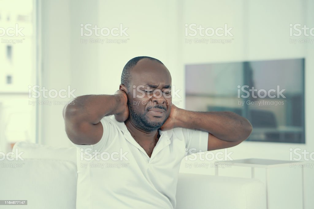 Elderly african man suffering from neck pain at home on couch. Males...
