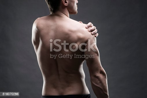 istock Pain in the shoulder on gray background 516070286