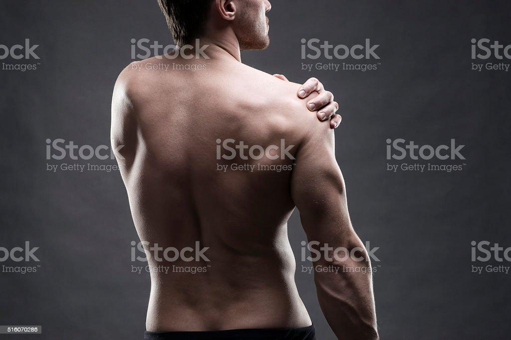 Dolor en el hombro sobre fondo gris - foto de stock