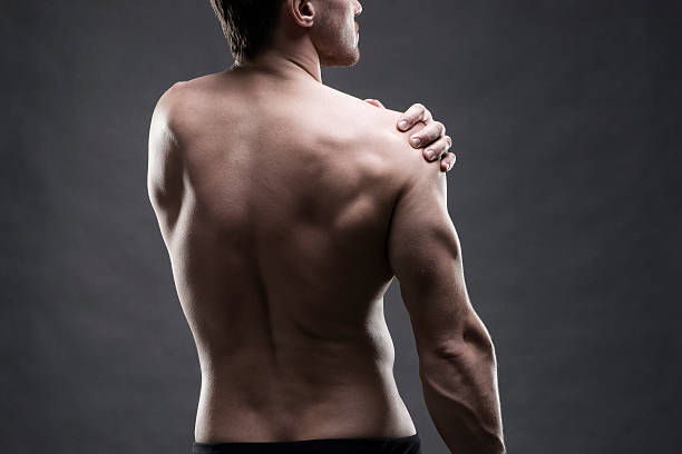 Pain in the shoulder on gray background stock photo