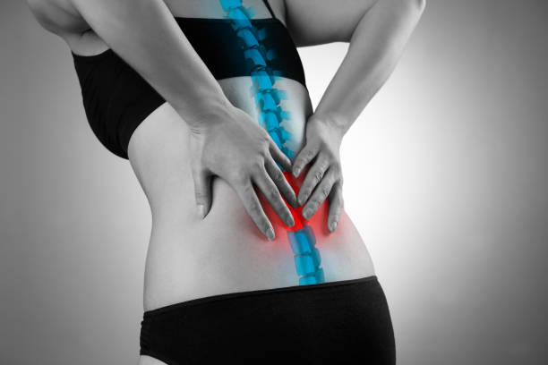 Pain in the spine, woman with backache, injury in the lower back Pain in the spine, woman with backache, injury in the lower back, black and white photo with highlighted skeleton human vertebra stock pictures, royalty-free photos & images