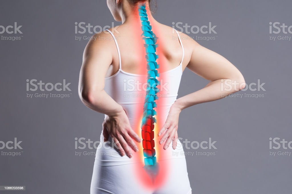Pain in the spine, woman with backache on gray background, back...