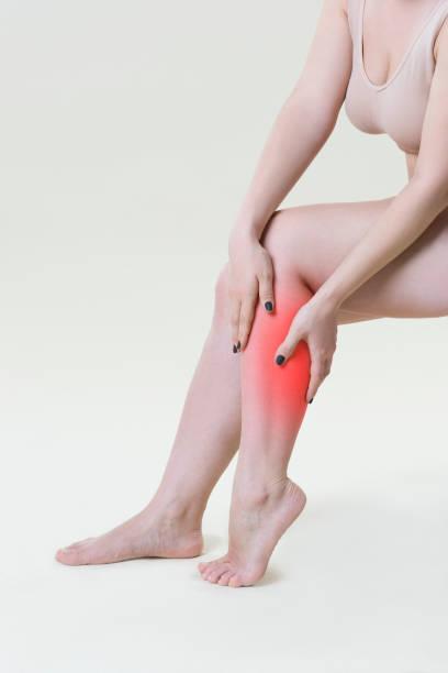 schmerzen in frauenbeine, massage der weiblichen füße auf beige hintergrund - wadenkrämpfe was tun stock-fotos und bilder