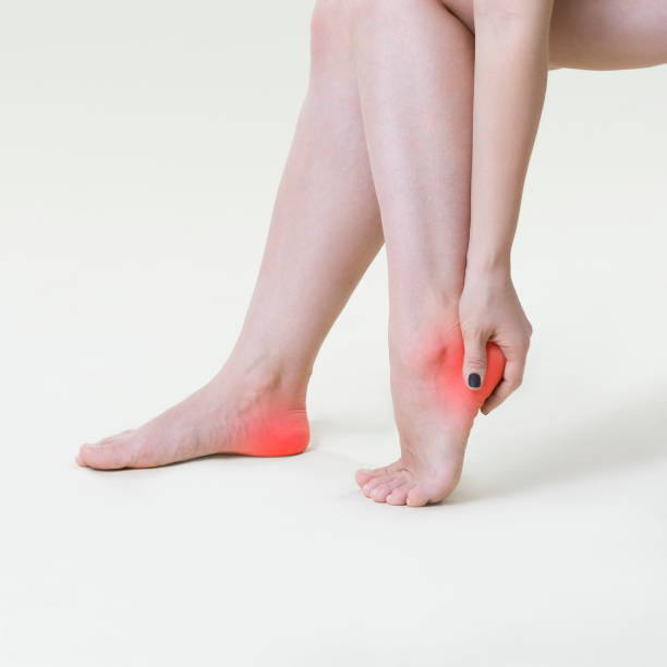 pain in woman's legs, massage of female feet on beige background - human foot stock photos and pictures