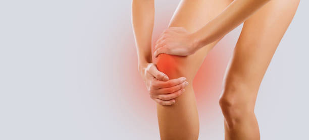 Pain, injury to the knee. Pain, injury to the knee. A woman holds her knee with her hand. rheumatism stock pictures, royalty-free photos & images
