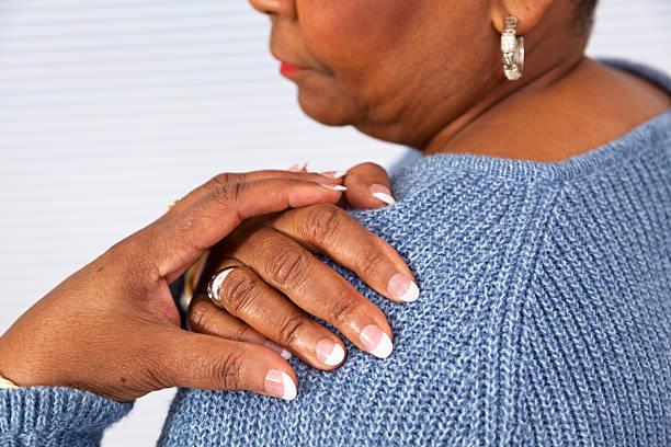 Dolore: Di Discesa africana Senior donna spalla nel dolore - foto stock