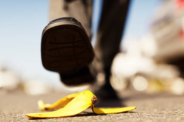 Painful accident about to happen. Foot approaching banana peel. An unidentified  male walker's foot in a formal shoe is about to step on a dropped banana peel - a painful accident waiting to happen! Focus on the banana skin. banana peel stock pictures, royalty-free photos & images