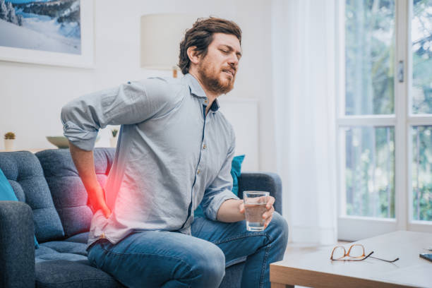 Painful guy aching from pain in back or reins at home stock photo