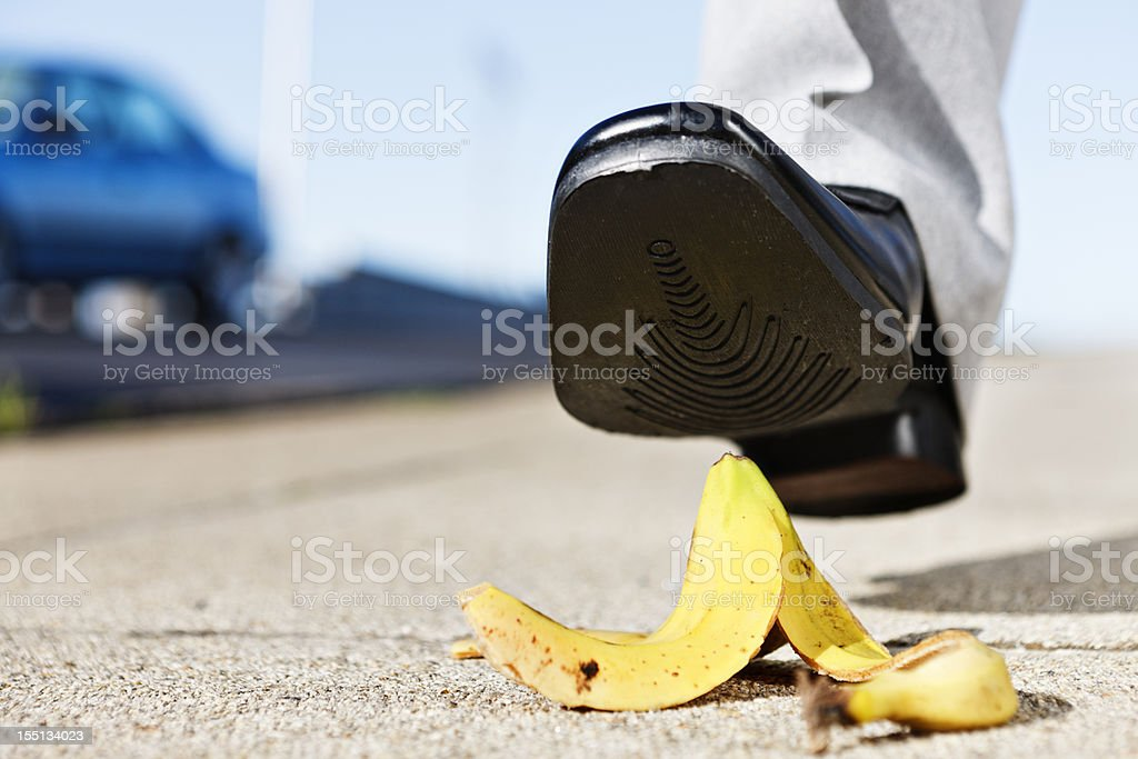 Painful slip coming as man's foot approaches banana peel royalty-free stock photo