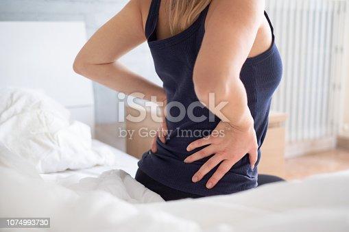 istock Painful woman awakening and feeling back pain 1074993730