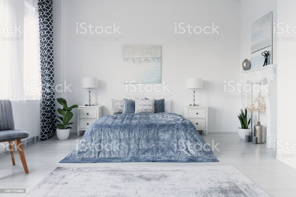 Paining above big comfortable bed in luxury new york style bedroom, real photo stock photo