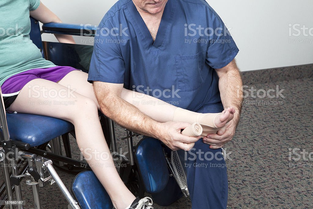 Pains and Sprains- tending to a sprained ankle royalty-free stock photo