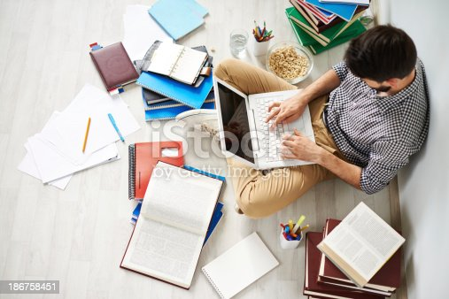 Young man sitting on the floor using laptop surrounded with great number of different things