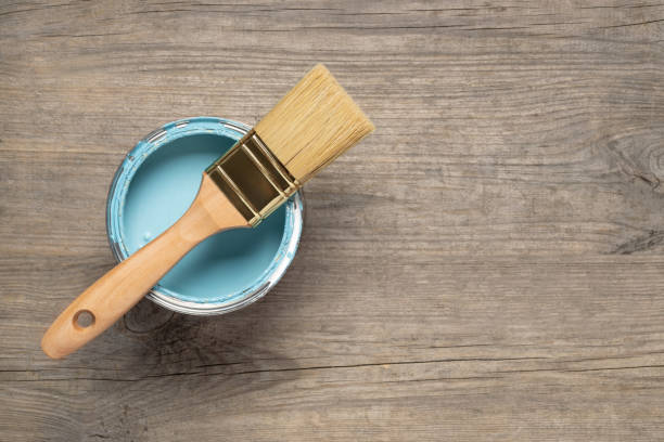 Paint brush and can on wooden table stock photo