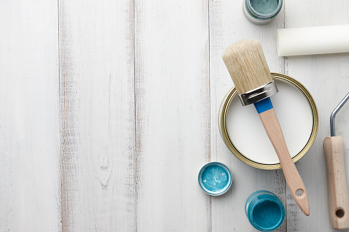 Paint, brush and other painting supplies on white wooden table