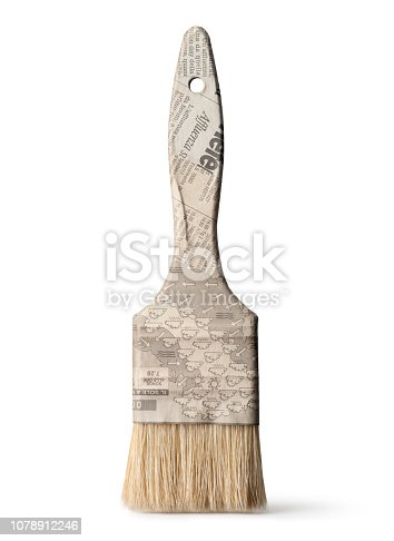 Paint brush covered with old newspaper. Photo on white background.