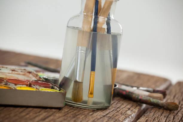 pinsel in ein glas, gefüllt mit wasser und wasserfarben - senior bilder wasser stock-fotos und bilder