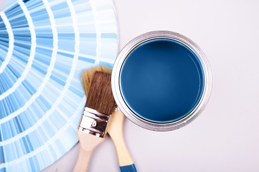 istock Paint brush laying on heap of color samples. open can of blue paint 1192070379
