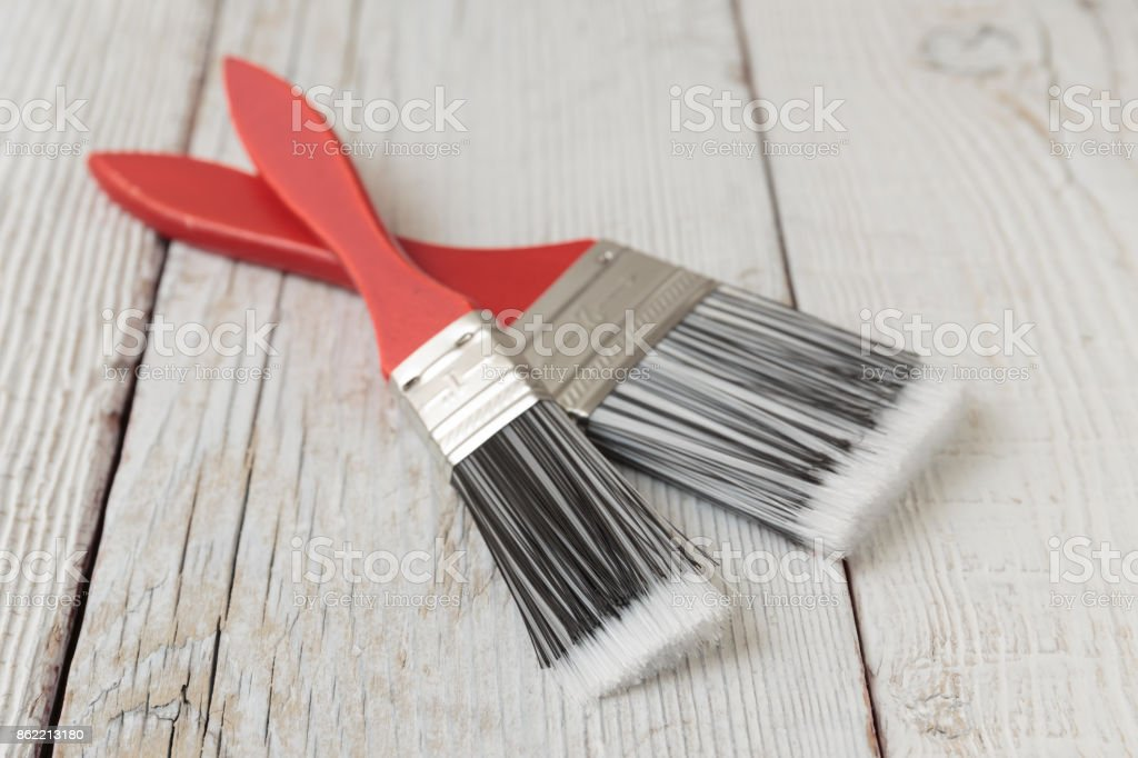 Paint brush on a white wooden board stock photo