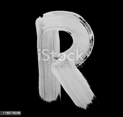 Paint brush stroke of letter, isolated on a black background. High detailed macro studio photographed handwriting.