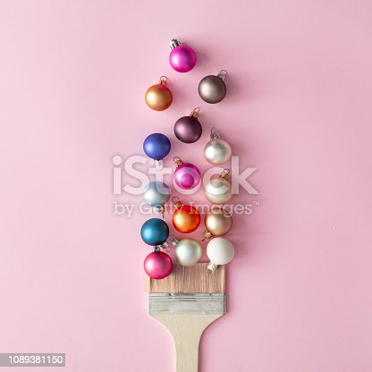 istock Paint brush with Christmas ornaments on pastel pink table. 1089381150