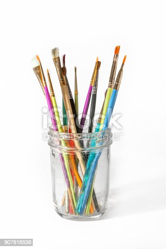 Paint brushes in a mason jar on white background