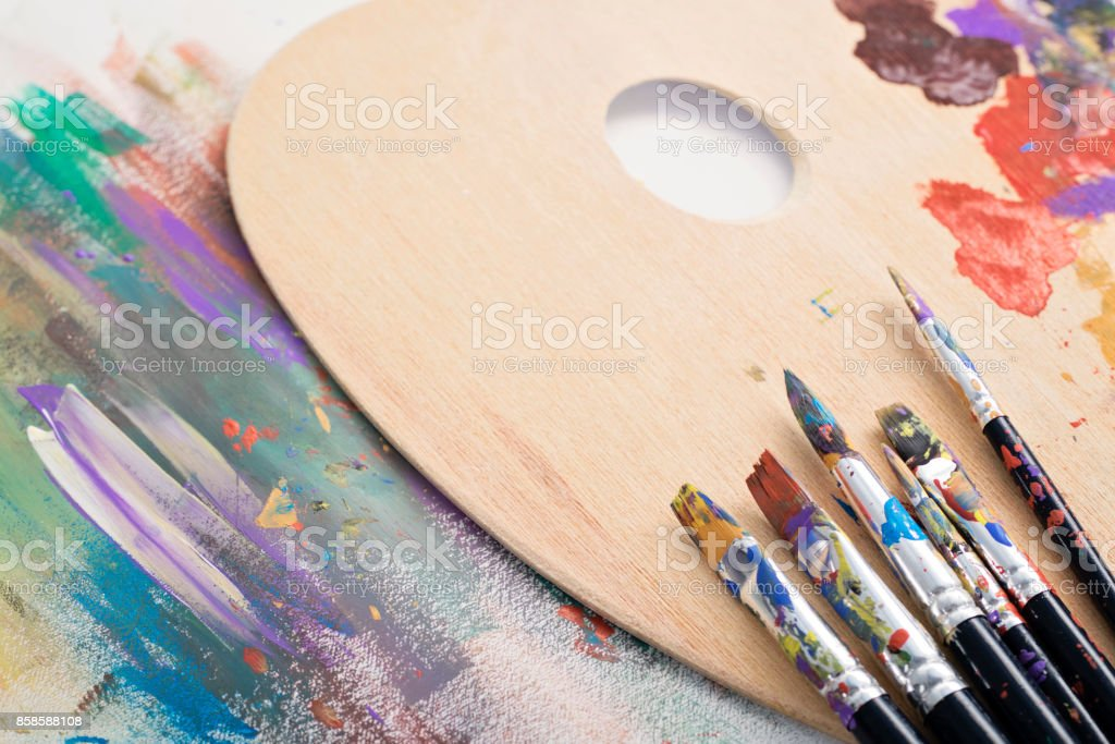 Paint brushes, palette and artwork stock photo
