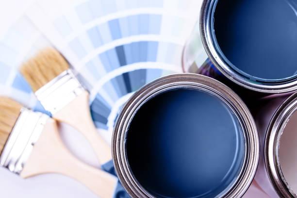 pędzle umieszczone na górze puszki wypełnione niebieską farbą. klasyczny niebieski kolor roku 2020. - malarstwo zdjęcia i obrazy z banku zdjęć