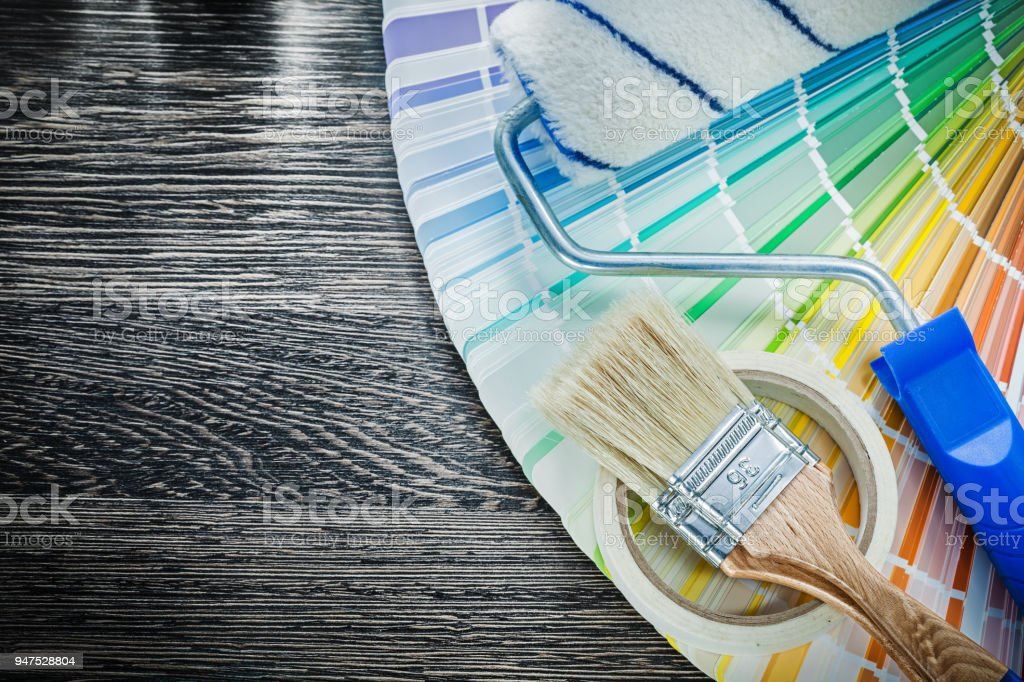 Paint brushes roller color sampler adhesive tape on wooden board stock photo