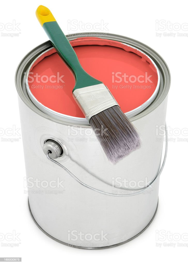 Paint bucket filled with red orange paint with brush stock photo