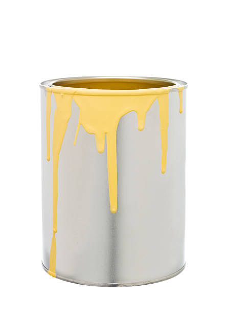 Paint Can with Yellow spill stock photo