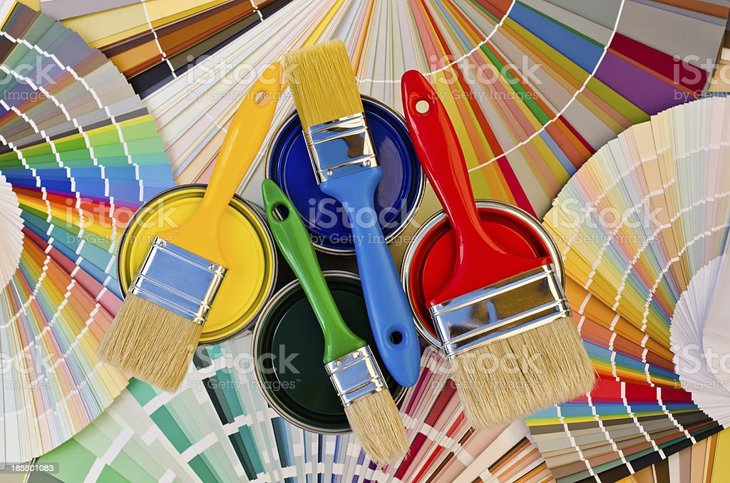 Paint cans and brushes on stripes of color sample. stock photo
