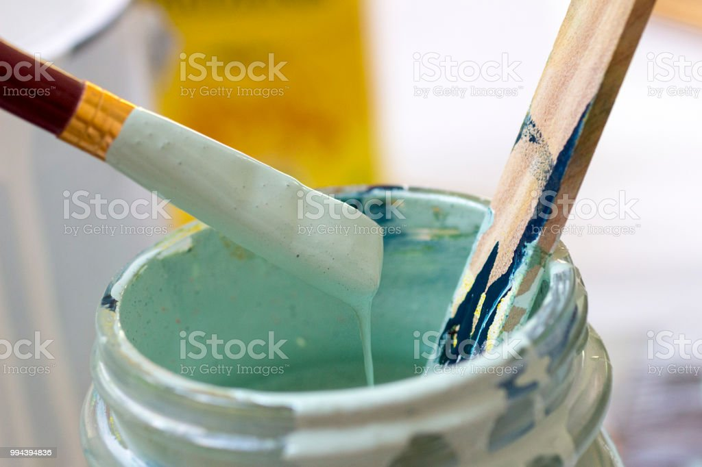 Paint, paintbrush and wooden stick. stock photo