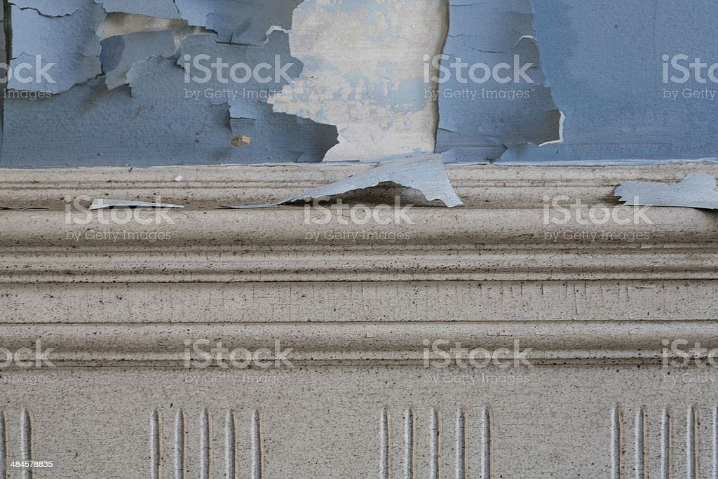 Paint peeling on an old plaster wall above molding stock photo