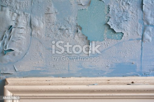 Paint peeling on an old plaster wall above molding