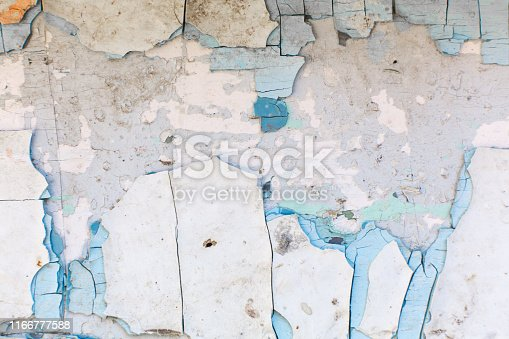 paint peels off the wall. Mill painting with a large number of layers of old paint.
