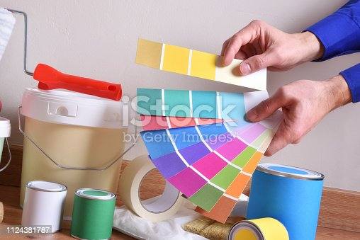 istock Paint pots composition on parquet and hands with color palette 1124381787