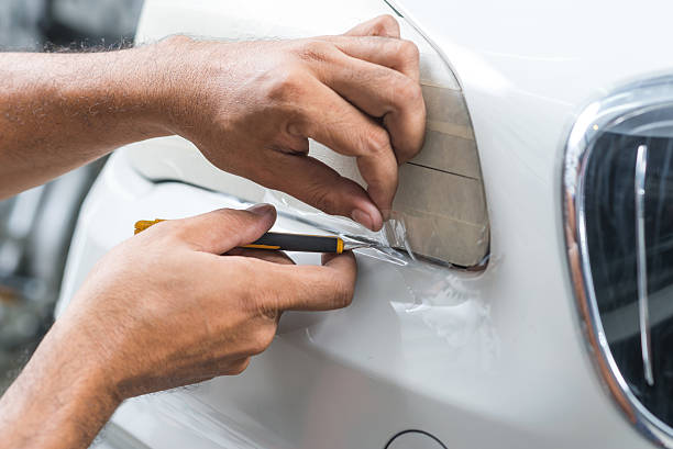 Paint protection film series : Cutting paint protection film stock photo