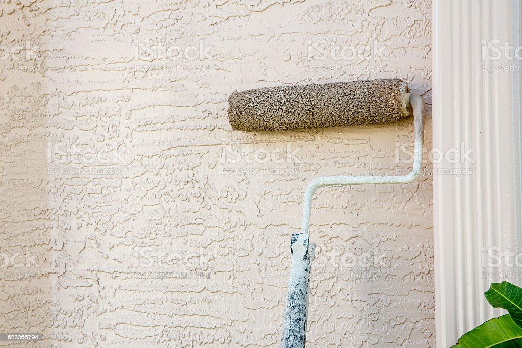 Paint roller attached to pole on outside wall of house stock photo