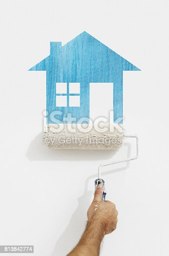 istock paint roller hand with blue house symbol painting on wall isolated on white 813842774