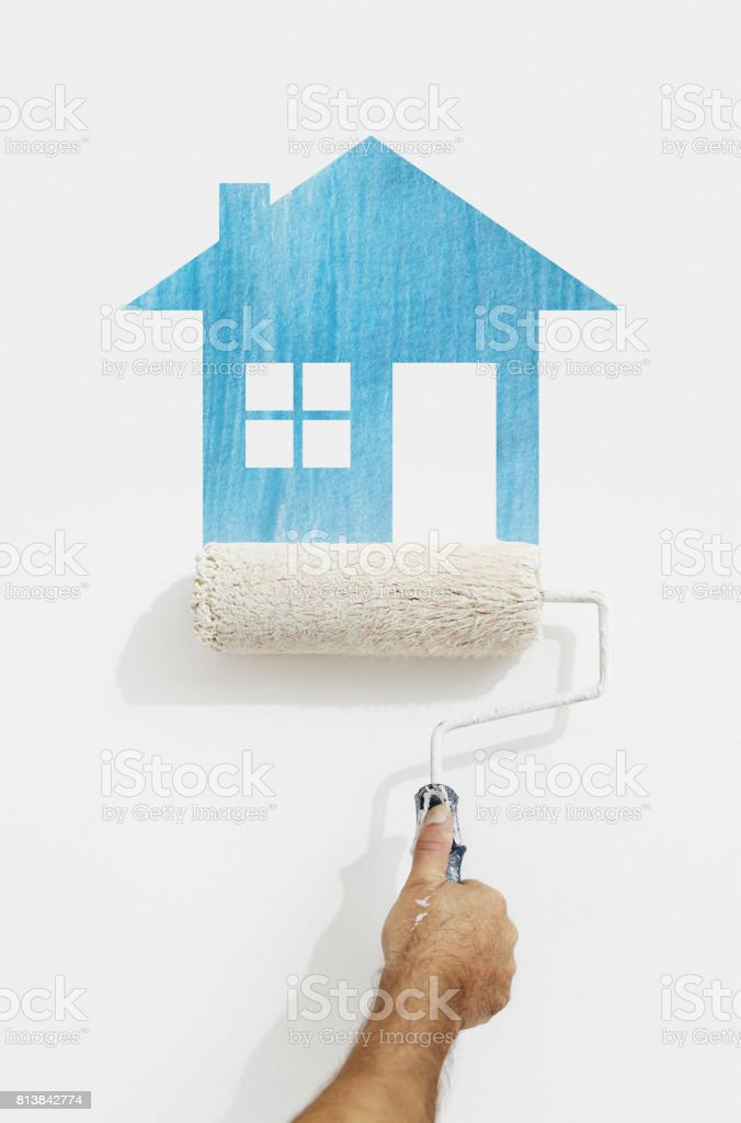 paint roller hand with blue house symbol painting on wall isolated on white stock photo