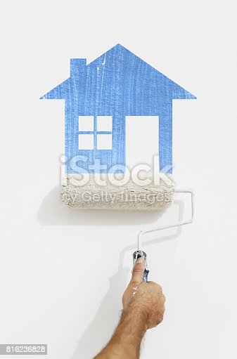 istock paint roller hand with blue house symbol painting on wall isolated on white 816236828