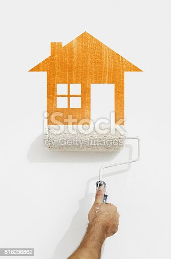 istock paint roller hand with orange house symbol painting on wall isolated on white 816236862
