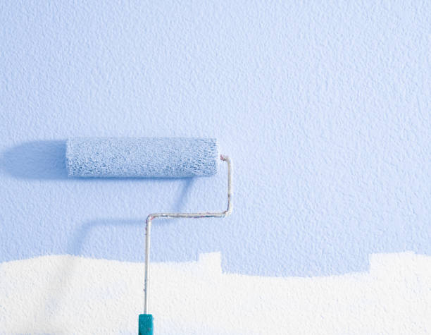 Paint roller on wall stock photo