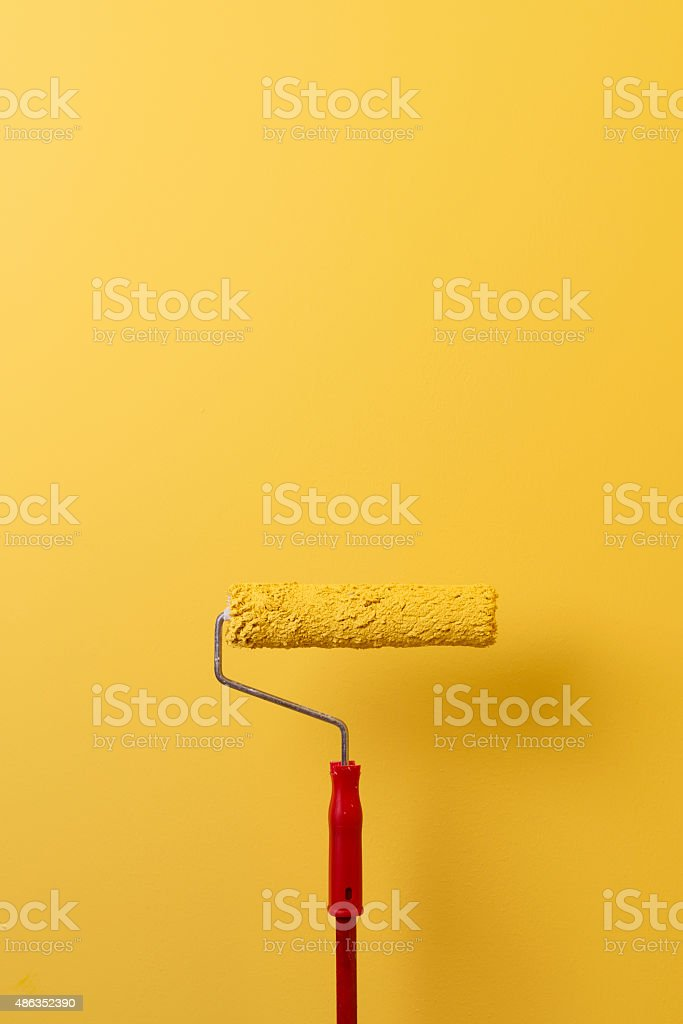 Paint Roller Painting The Wall In Yellow stock photo