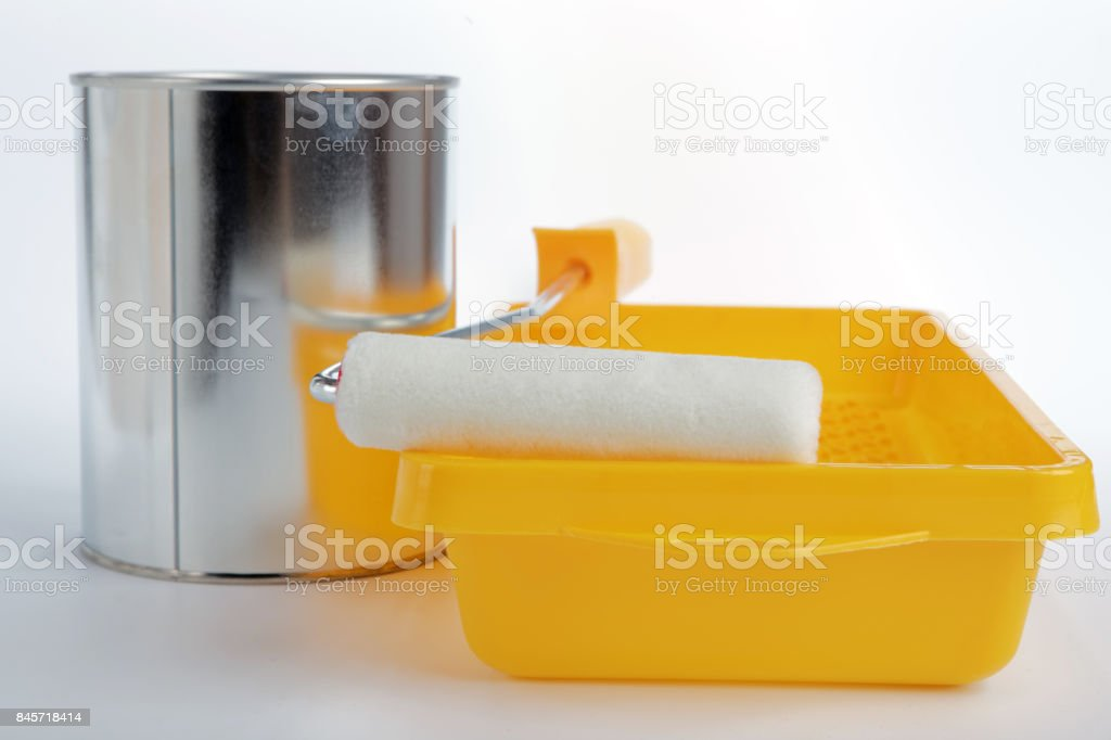 Paint roller, tray, and a can with paint stock photo