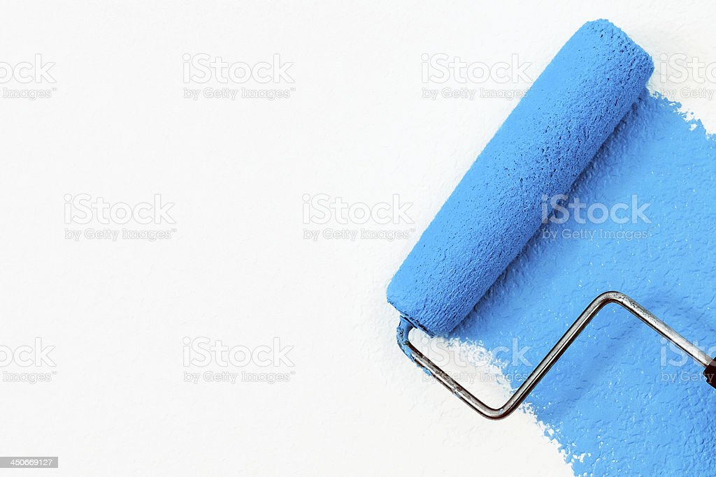 Paint roller with blue paint on a white background stock photo