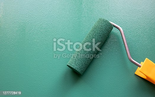 Paint roller with green colour on painted wooden surface. Chalk board. Painting and renovation.